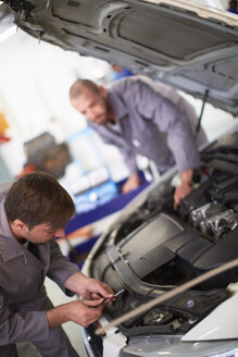 Two car mechanics at work in repair garage - ZEF000546