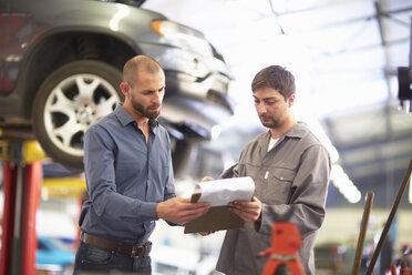 Car mechanic with client in repair garage - ZEF000553