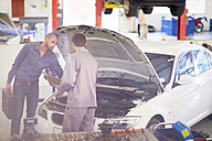 Car mechanic with client in repair garage - ZEF000554