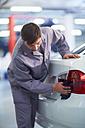 Car mechanic wiping car in repair garage - ZEF000556