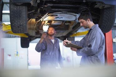 Two car mechanics at work in repair garage - ZEF000558