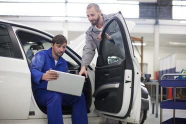 Two car mechanics with laptop in repair garage - ZEF000578