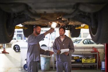 Two car mechanics at work in repair garage - ZEF000504