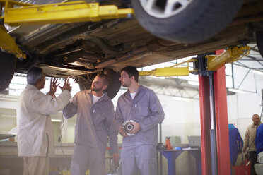 Two car mechanics with client in repair garage - ZEF000506