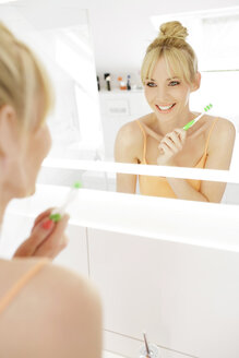 Woman looking at her mirror image while showing her teeth - GDF000425