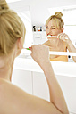 Woman looking at her mirror image while brushing teeth - GDF000426