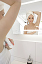 Mirror image of woman applying deodorant in the bathroom - GDF000431