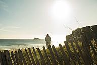 France, Brittany, Camaret-sur-Mer, senior woman standing at the coast - UUF001780