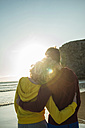 France, Brittany, Camaret-sur-Mer, teenage couple on the beach looking at sunset - UUF001791