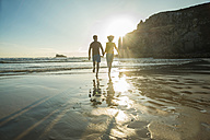 France, Brittany, Camaret-sur-Mer, teenage couple running on the beach - UUF001807