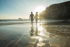 France, Brittany, Camaret-sur-Mer, teenage couple running on the beach - UUF001807
