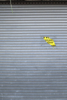 Spain, Catalonia, closed shop, gray roller shutter with yellow sticker - JMF000281