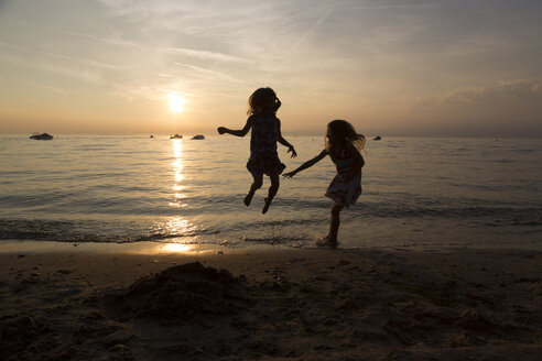 Italy, Lake Garda, two girls jumping on beach at sunset - SARF000843
