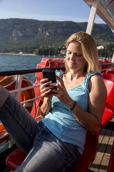 Italy, Lake Garda, woman with cell phone on tourboat - SARF000829