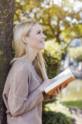 Smiling young woman with opened book leaning at tree trunk - GDF000441