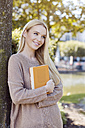 Portrait of smiling young woman with  book leaning at tree trunk - GDF000454