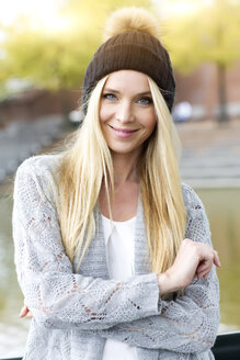 Portrait of smiling young woman wearing bobble hat and cardigan - GDF000447