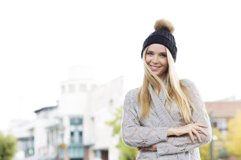 Portrait of smiling young woman wearing bobble hat and cardigan - GDF000449