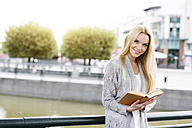 Portrait of smiling young woman with opened book - GDF000450
