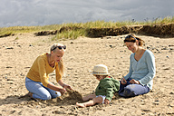 France, Britanny, Sainte-Anne-la-Palud, mother and her two daughters sitting on beach dune - LAF001140