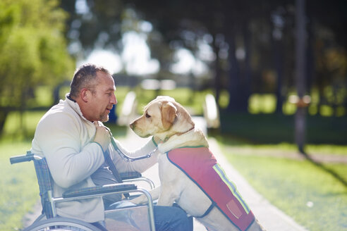 Man in wheelchair with dog in park - ZEF000386