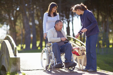 Man in wheelchair with two women and dog in park - ZEF000393