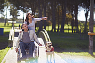 Woman with man in wheelchair and dog in park - ZEF000396