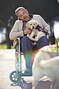 Man in wheelchair with dog puppy in park - ZEF000397
