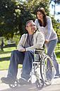 Woman pushing man in wheelchair - ZEF000403