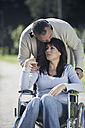 Man consoling sad woman in wheelchair - ZEF000410