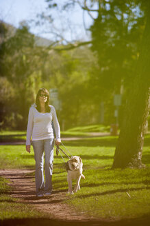 Visually impaired woman walking with guide dog in a park - ZEF000864