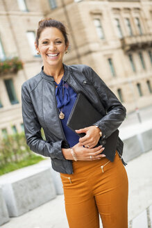 Portrait of happy young woman wearing leather jacket holding a folder - JUNF000076