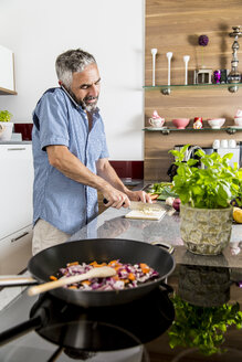Austria, Man in kitchen using smart phone - MBEF001238