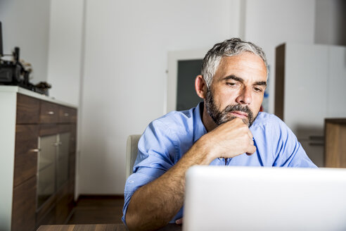 Portrait of businessman working with laptop at home office - MBEF001182