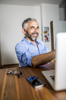 Portrait of smiling businessman at home office - MBEF001183