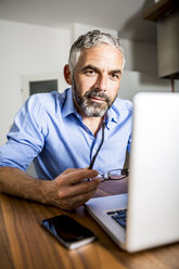 Portrait of businessman working with laptop at home office - MBEF001290
