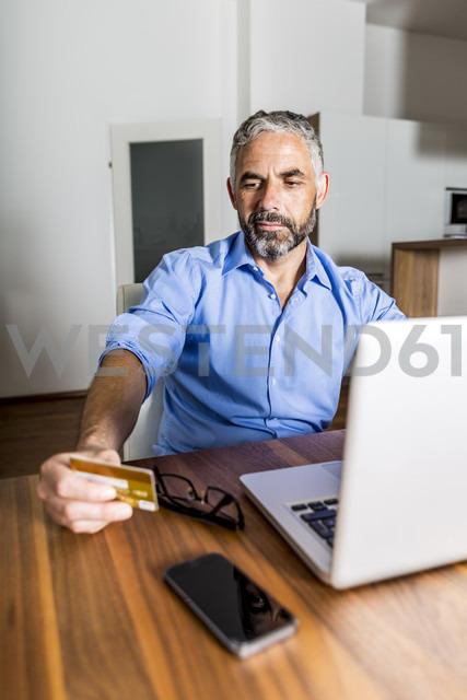 Portrait of businessman using his creditcard for online banking - MBEF001291 - Martin Benik/Westend61
