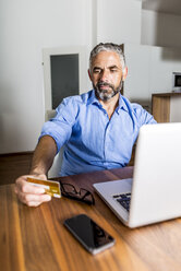 Portrait of businessman using his creditcard for online banking - MBEF001291