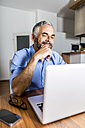 Portrait of smiling businessman working with laptop at home office - MBEF001292