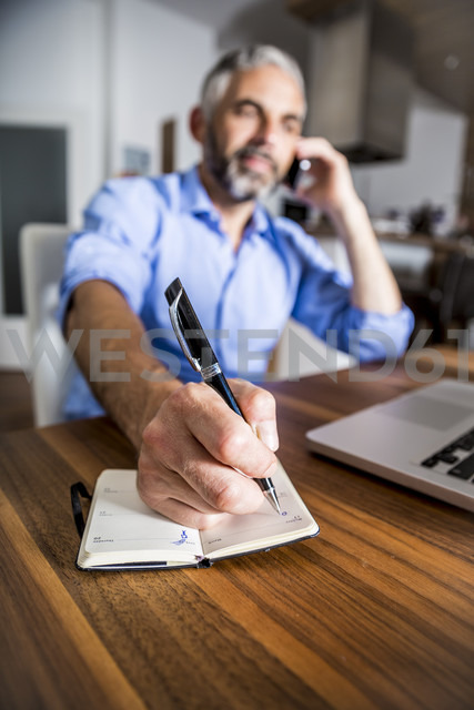 Businessman telephoning with his smartphone while making notes - MBEF001295