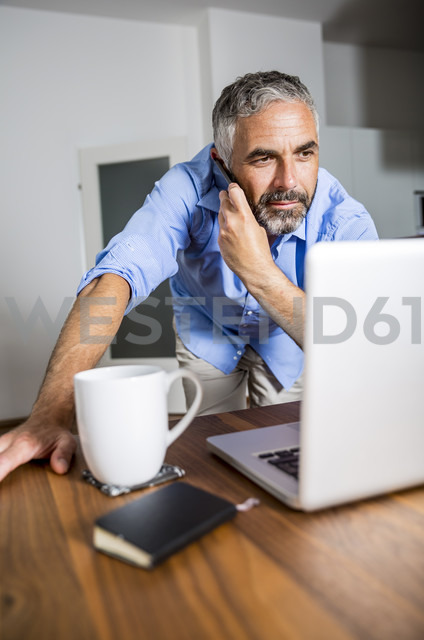Businessman telephoning with his smartphone while looking at his laptop - MBEF001298