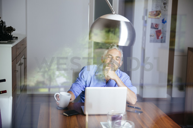 Pensive businessman working with laptop at home office - MBEF001186