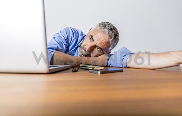 Tired businessman with laptop at home office - MBEF001304