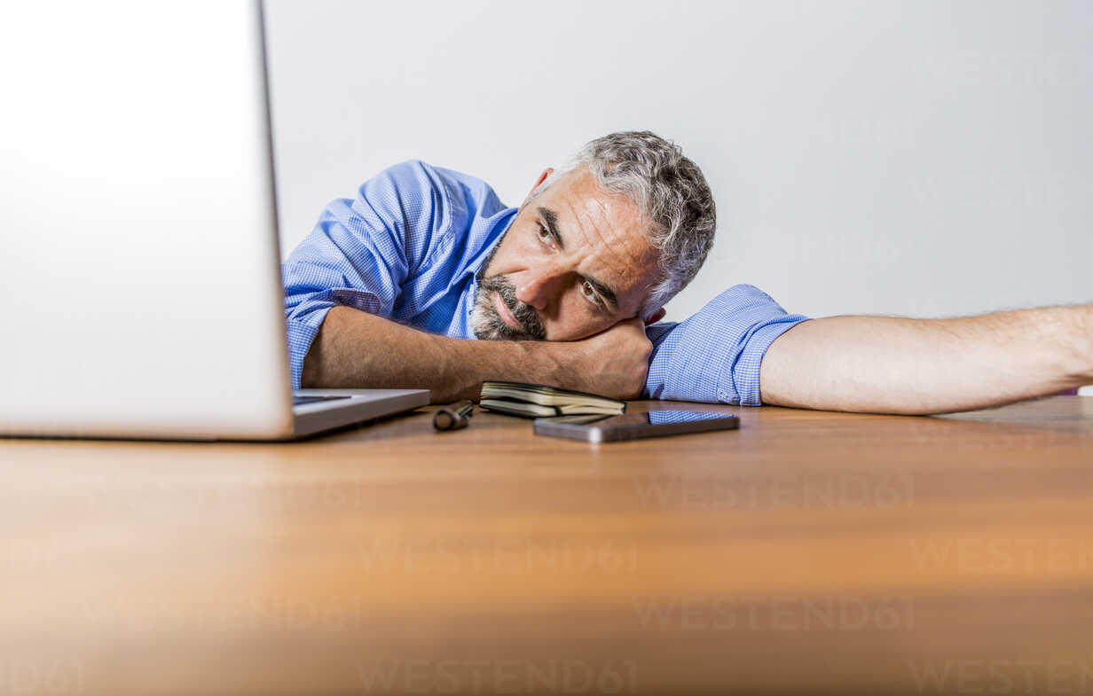 Tired businessman with laptop at home office - MBEF001304 - Martin Benik/Westend61