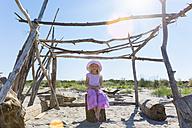 Italy, Veneto, girl sitting in self-made beach hut - HSIF000338