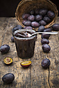 Preserving jar of plum jam and plums on wooden table - LVF001871