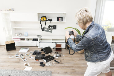 Woman photographing chaos after burglary when coming back in her one-family house - ONF000610