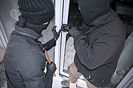 Two burglars opening terrace door of an one-family house with hammer and crowbar at daytime, partial view - ONF000622