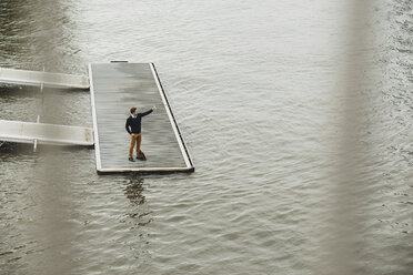 Germany, Hesse, Frankfurt, young man standing on a jetty taking a selfie with his digital tablet - UUF001829