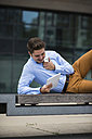 Germany, Hesse, Frankfurt, young man lying on a bench using his digital tablet - UUF001843